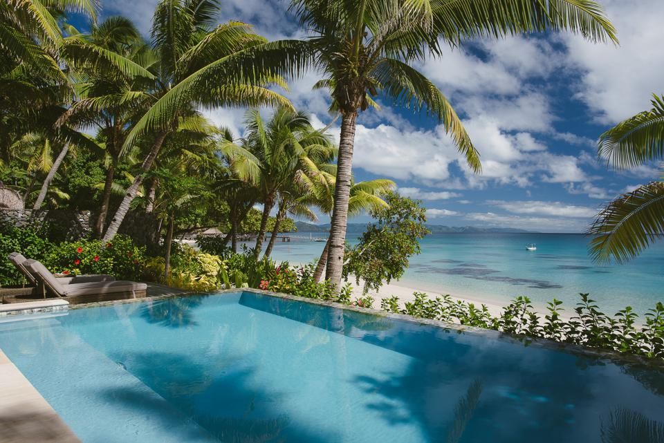 An infinity-edge pool surrounded by palm trees overlooks the beach on Kokomo Private Island.