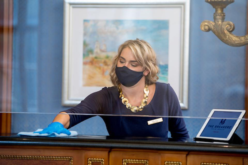 Guest and employee. health and safety are front and center at The Breakers; Front desk receptionist cleaning her station