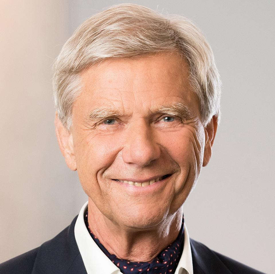 an older white man with white blond hair and a suit jacket smiling into camera