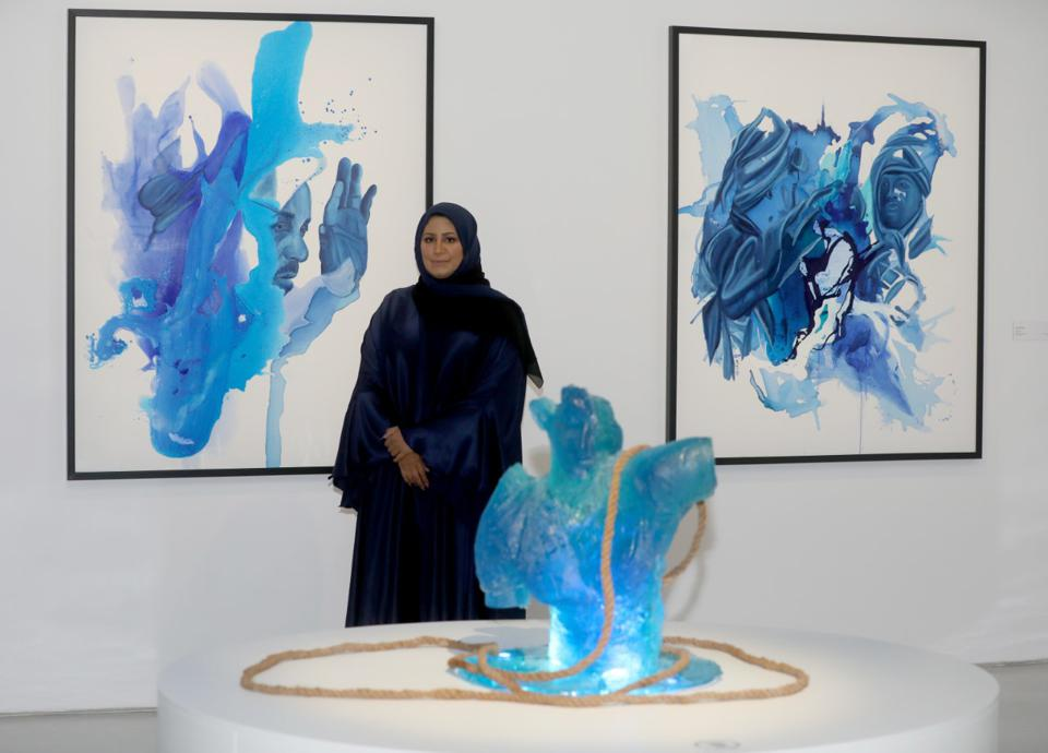 Muna Al-Bader standing in front of her gallery pieces.