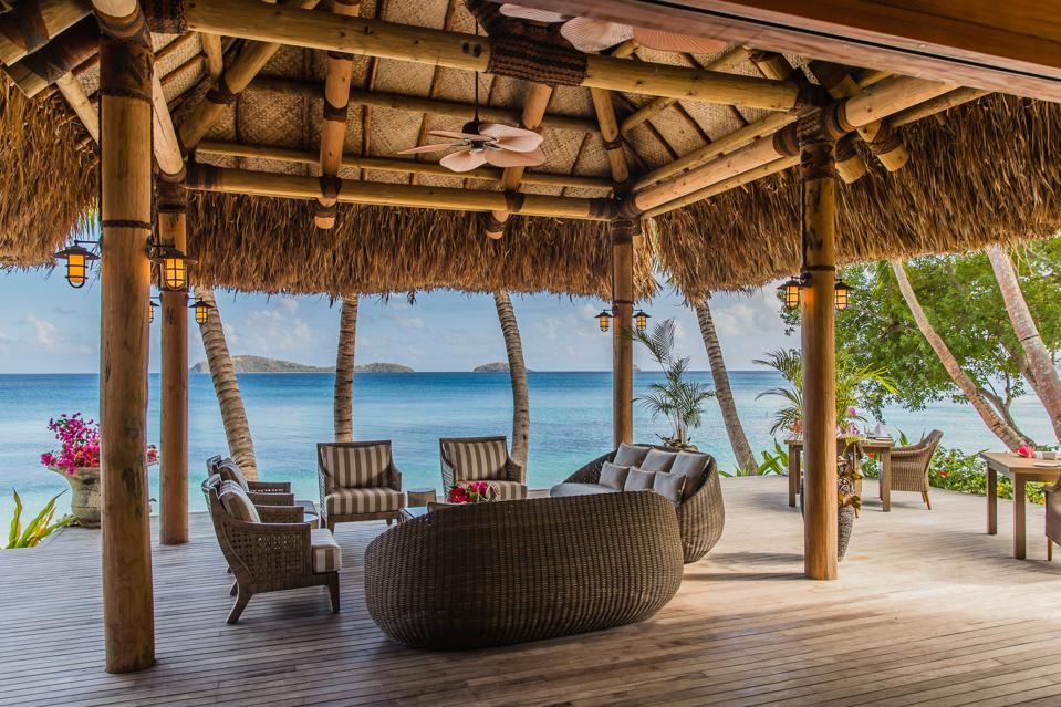 An open-air seating area beneath a canopy overlooks the crystalline seas at Kokomo Private Island.