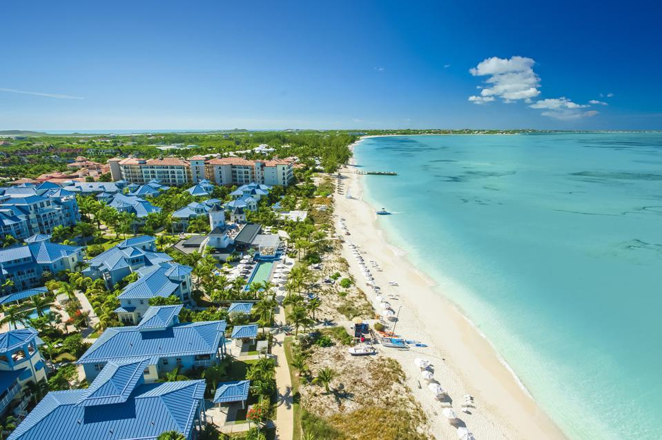 An aerial view of the resort with several buildings and palm trees on the left, a white sand beach in the center, and a turquoise calm sea on the right