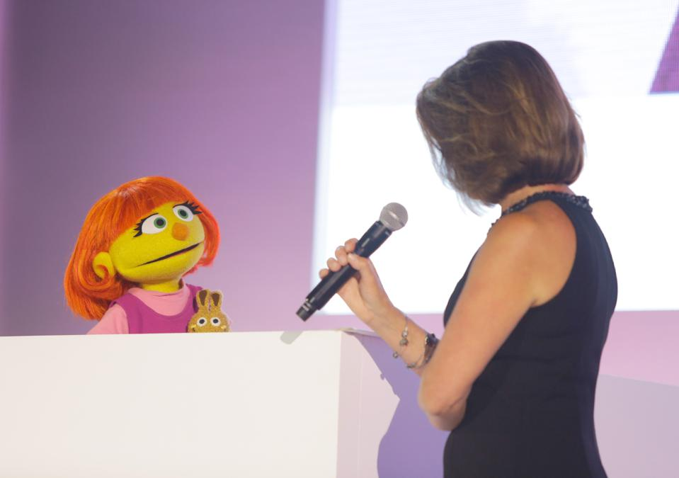 The muppet Sesame Street Julia looks at a presenter with a microphone who has her back to the camera