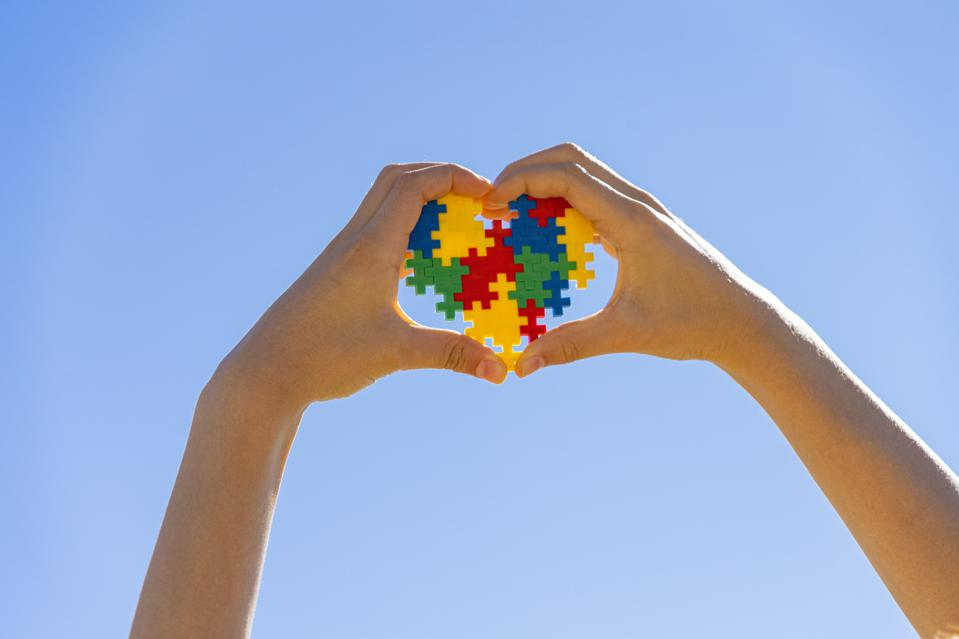 Child's hands in the shape of a heart holding colorful puzzle pieces in the rough shape of a heart on blue sky background.