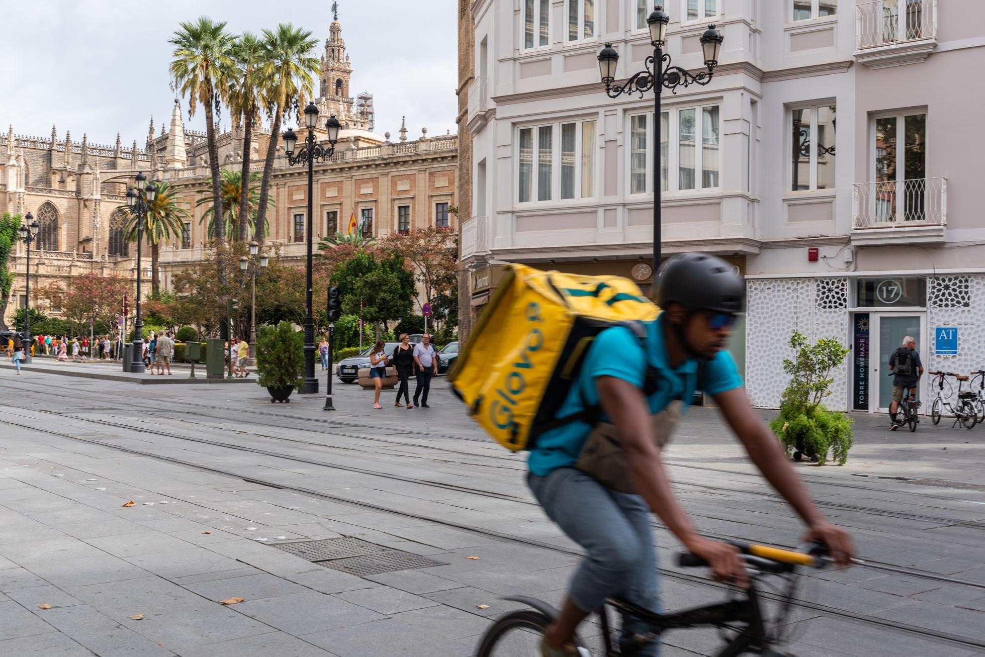 Glovo delivery man riding bicycle on the street...