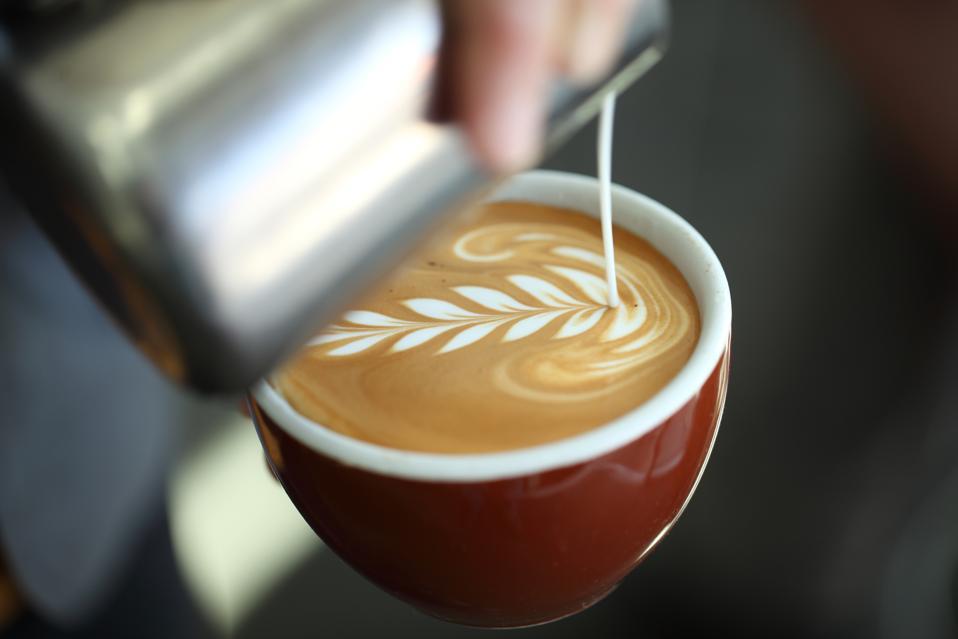 Barista pouring milk into cappuccino, Oakland, California, USA