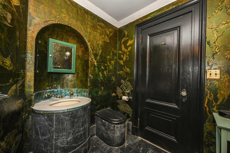 A sink with black and gold murals on the wall.