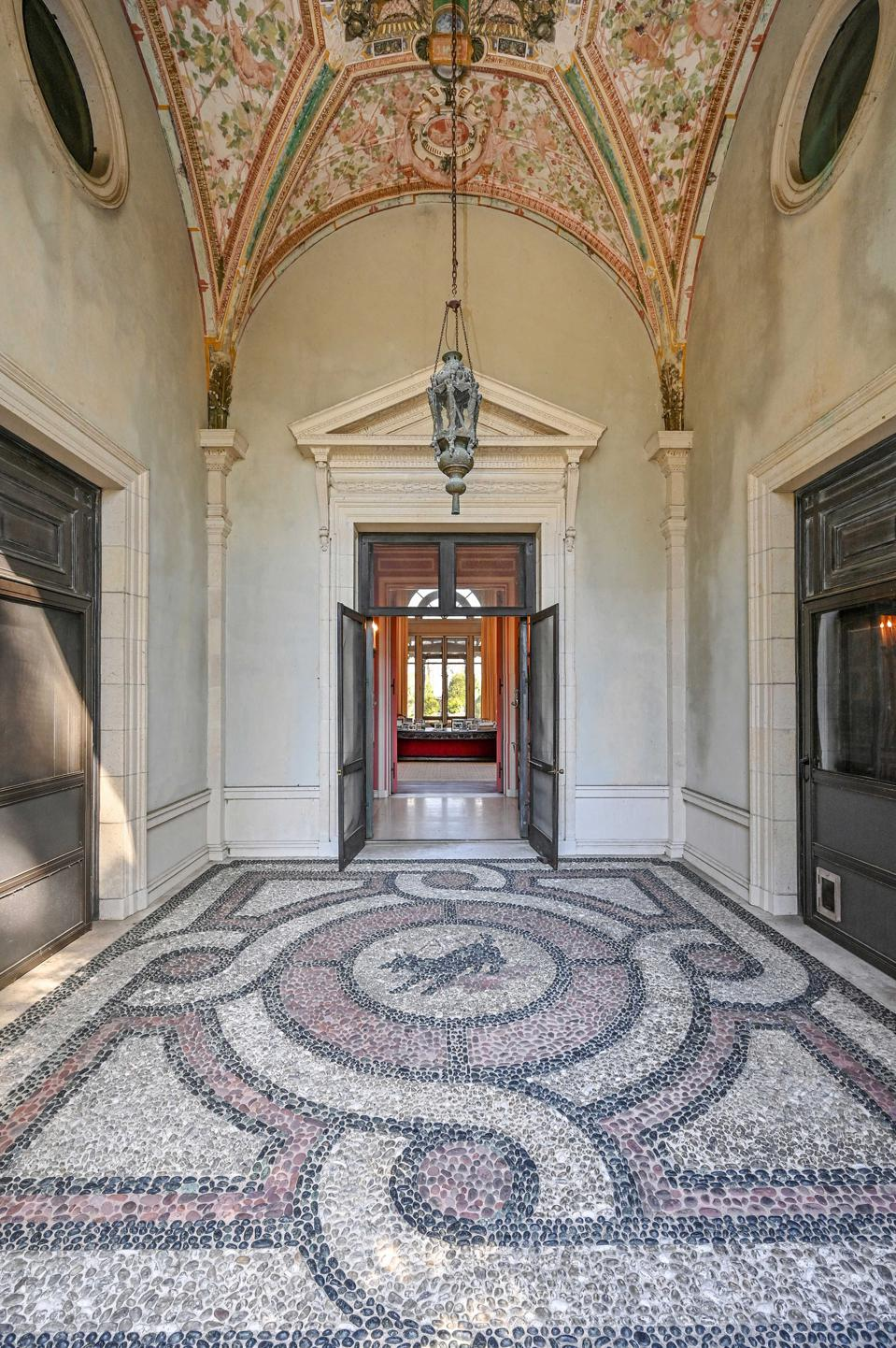 An entryway with a taupe and red mosaic stone floor.