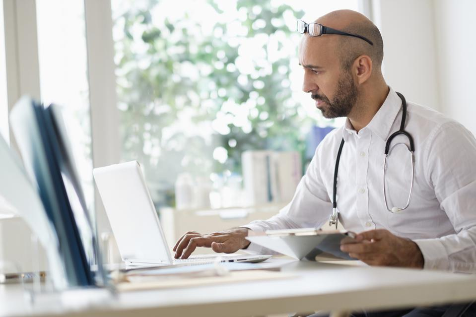 Concentrated doctor working with laptop at desk in office