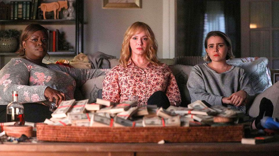 Beth, Annie and Ruby sit on a couch with lots of money