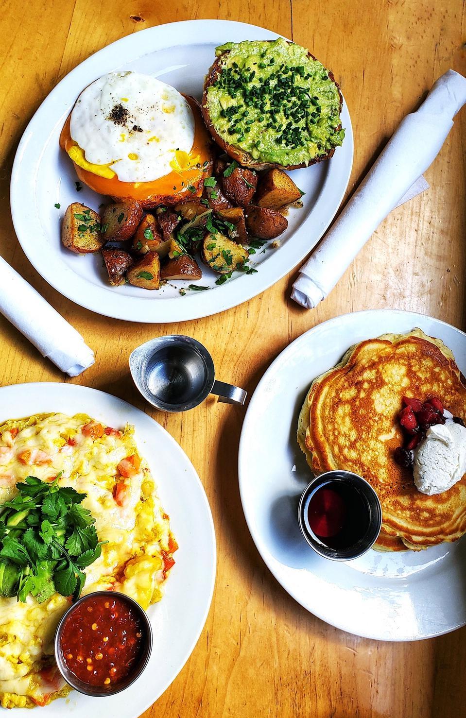 Fried egg sandwich, veggie mess, pancakes on table