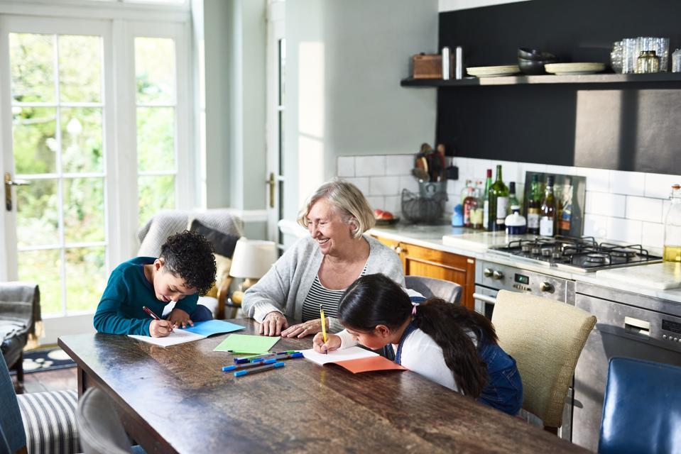 Grandmother homeschooling grandchildren at dining table