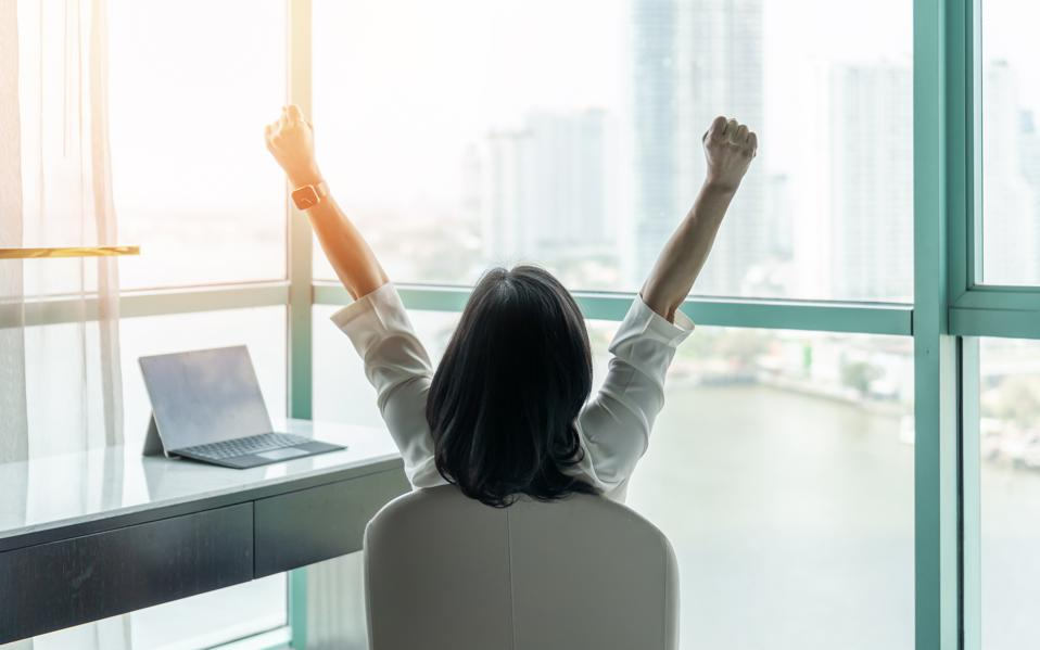 Business achievement concept with happy businesswoman relaxing in office or hotel room, resting and raising fists with ambition looking forward to city building urban scene through glass window
