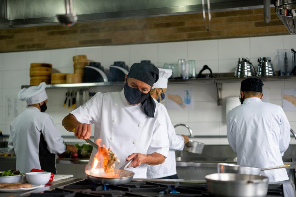 Chef wearing a facemask while working at a restaurant during the pandemic