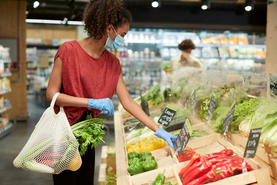 One millenial costumer choosing vegetables in a grocery store.