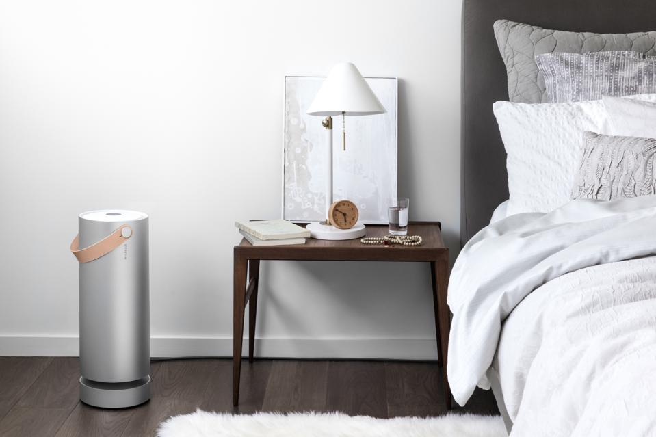 Molekule Air air purifier set up next to a bed with white bedding