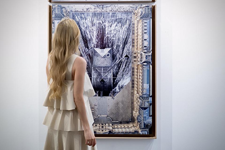 Nel-Olivia Waga at Galerie Perrotin Booth at Art Dubai 2021 in front of ″JR au Louvre et le Secret de la Grande Pyramide, Diptyque ©