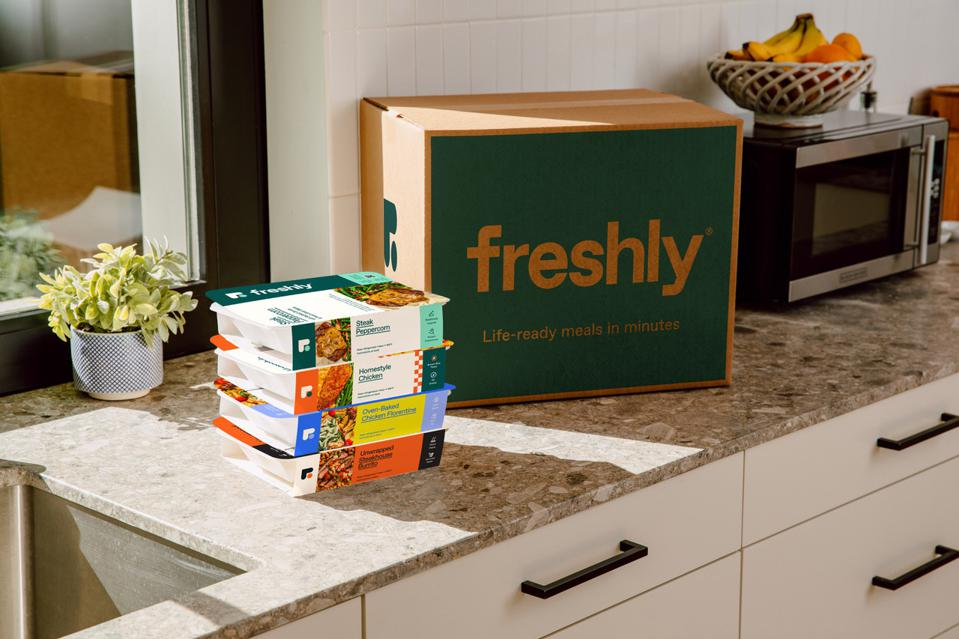 A photograph of a box of Freshly meals show the meals unboxed on a counter next to a microwave. The healthy meals are shipped fresh, not frozen and are re-heated in a microwave.