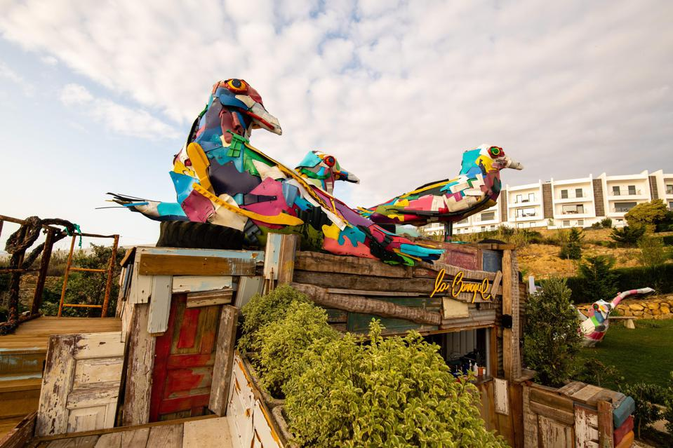 Colorful seagulls sit on the roof of the beach bar at You and the Sea hotel in Portugal