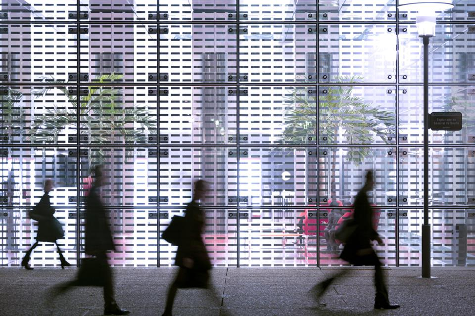Business people passing modern office building showing the importance of returning to the office.
