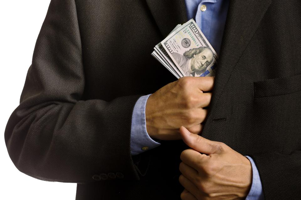 Corporate Businessman Slipping U.S. dollars Money into Suite Pocket
