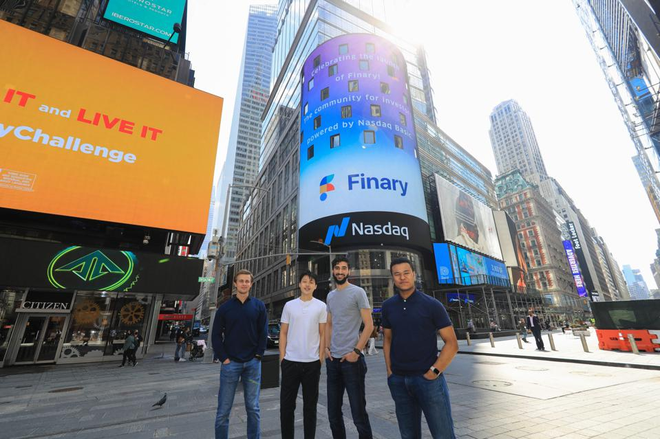 Four guys standing in Times Square.