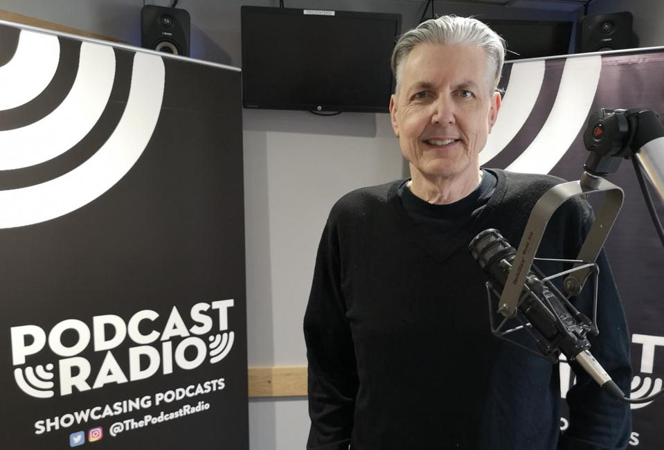 Gene Baxter standing next to a Podcast Radio sign