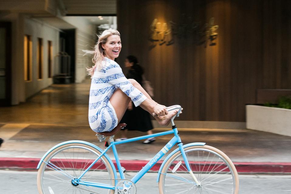 A young woman riding a bike near a hotel.