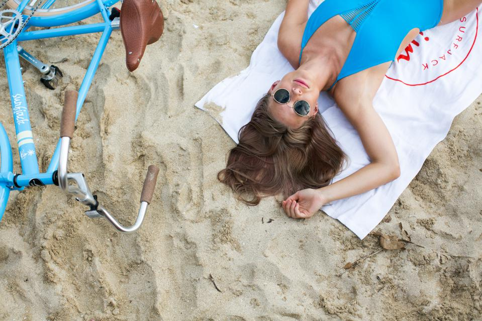 A woman lying on the beach in Hawaii with sunglasses.