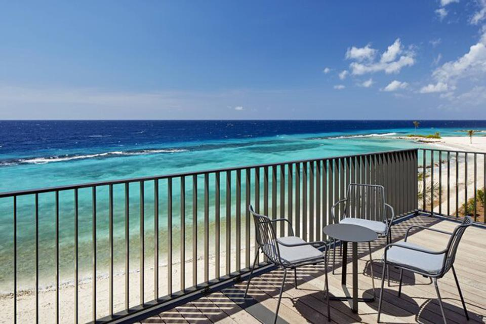 A deck with chairs near the ocean.