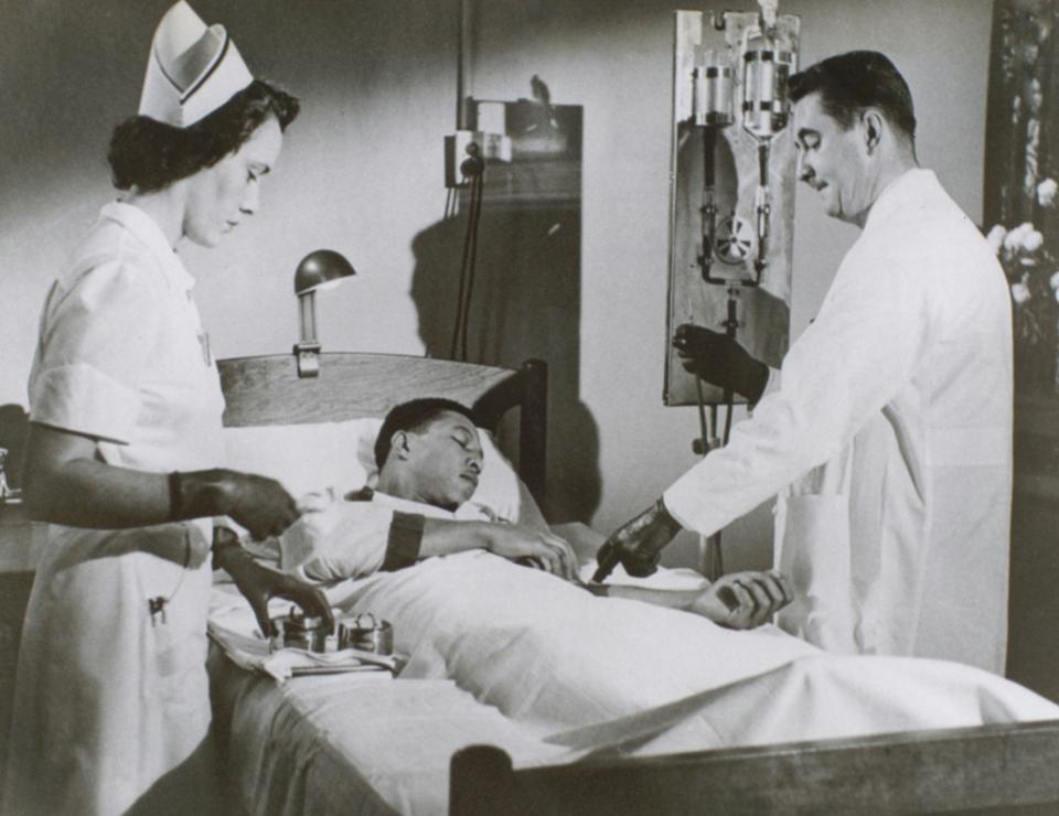 A Black patient being tended to by a White male doctor and White female nurse.