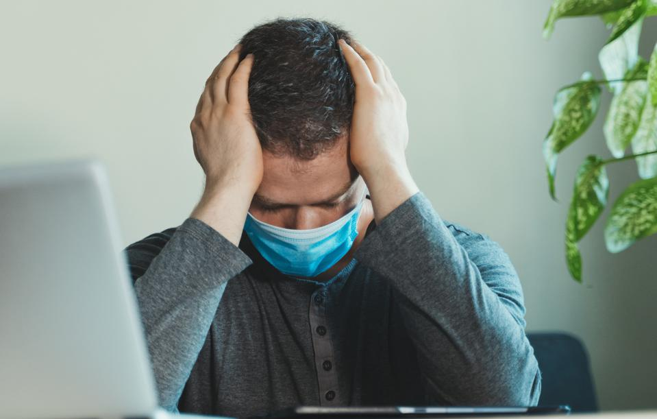Upset man in medical mask in the office.