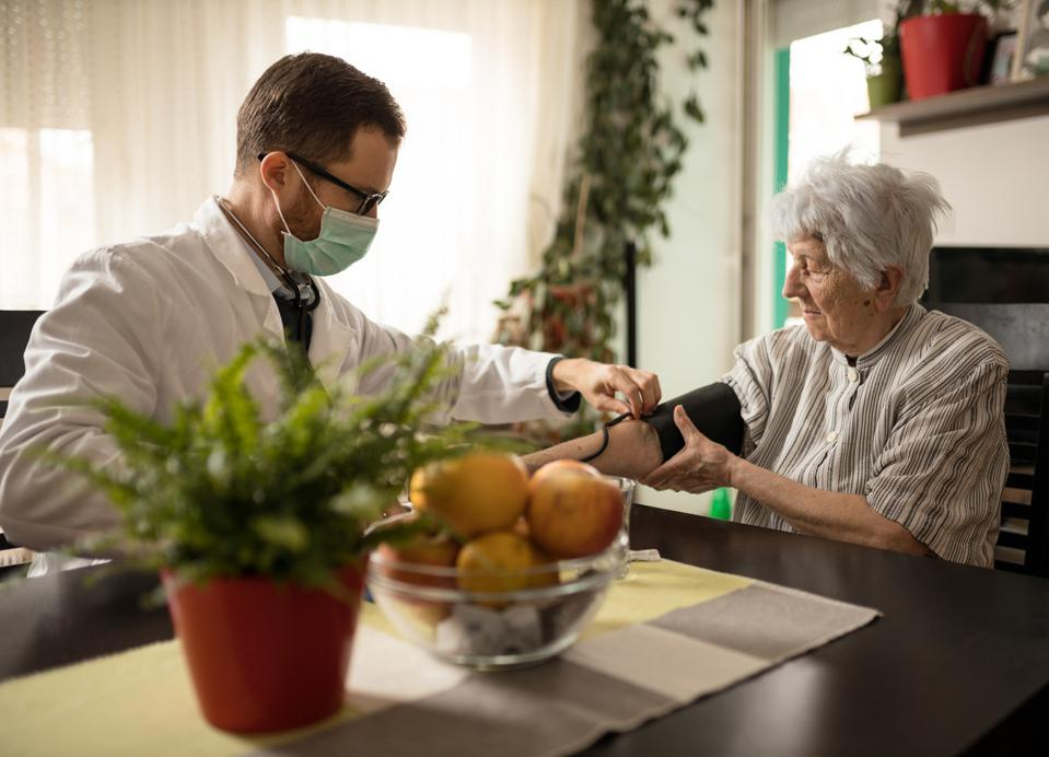 Doctor wearing face mask adjusting blood pressure gauge on woman's arm during house call medical check-up