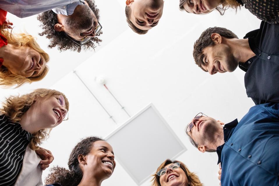 Smiling entrepreneurs huddling together in creative office