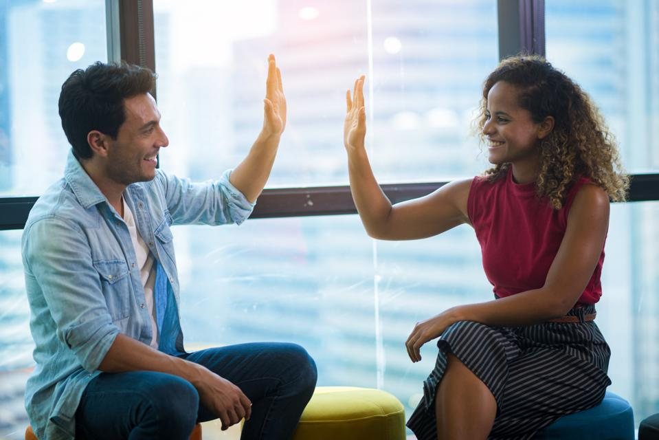 Smiling Colleagues Giving High-Five While Sitting In Office