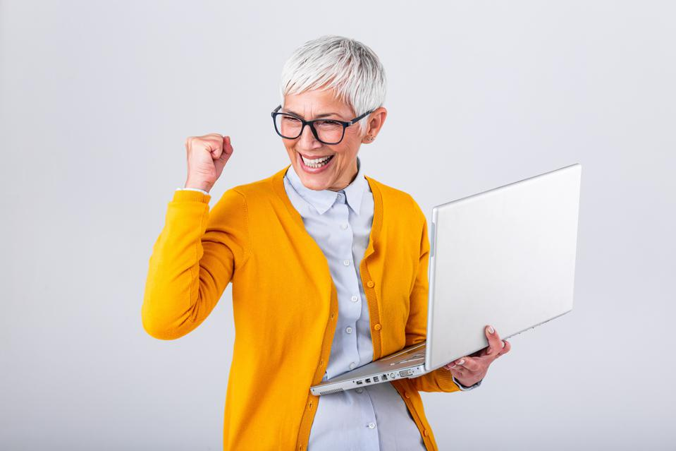 cheerful mature woman with a laptop computer and celebrating success