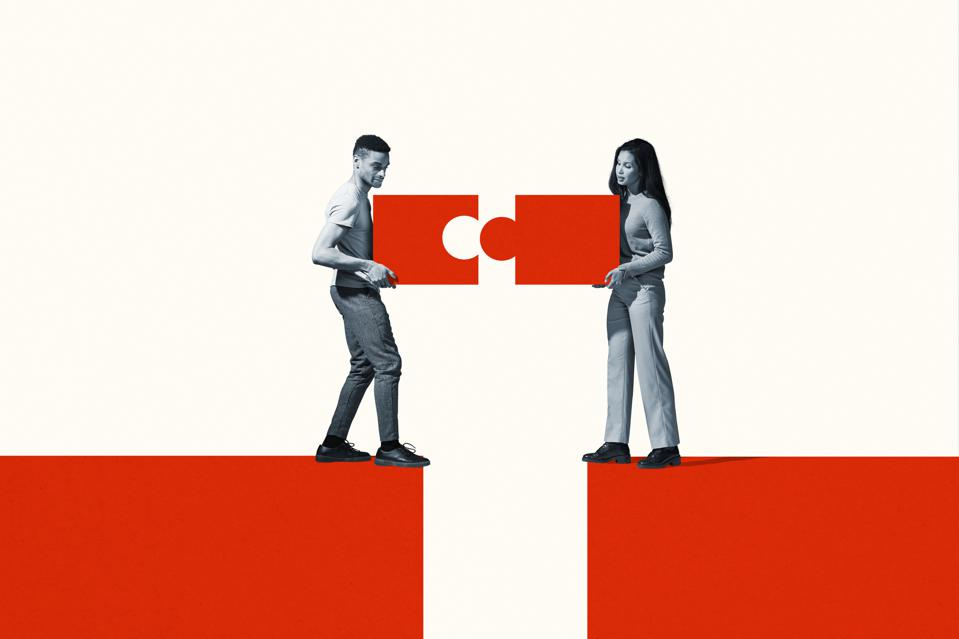 Man and woman positioning orange puzzle pieces