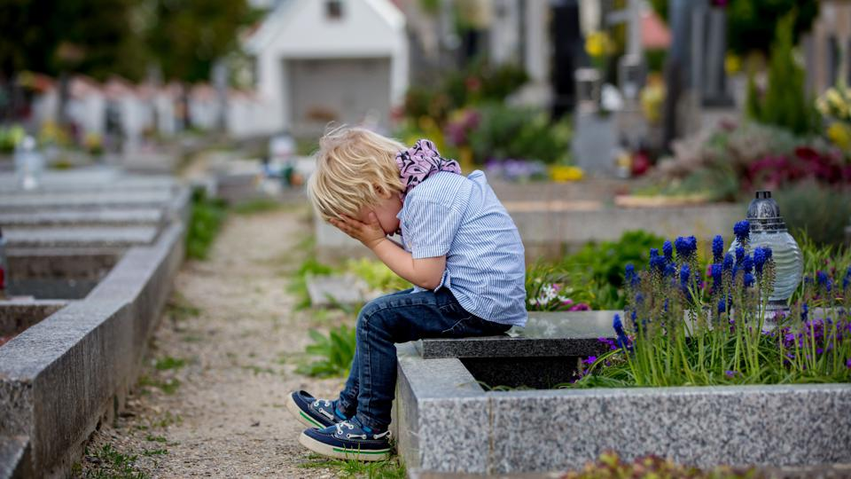 Little toddler boy, sitting on a grave in cemetery, sad and lonely, springtime
