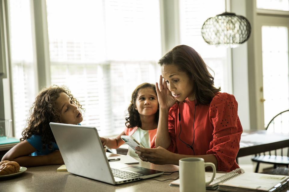 Mother working from home with children in background