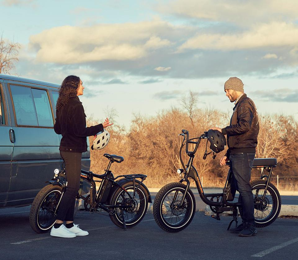 Young man and woman with their electric bikes.