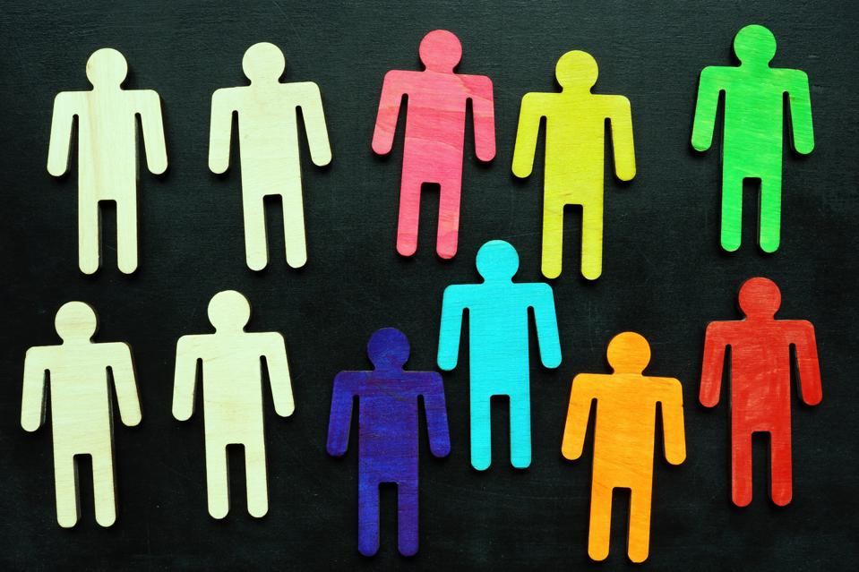 Equality and diversity concept. Multi-colored figurines on a blackboard.