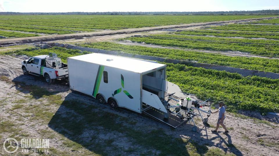 An image of a truck with a trailer and a man unloaded a Guardian Agriculture eVTOL drone.