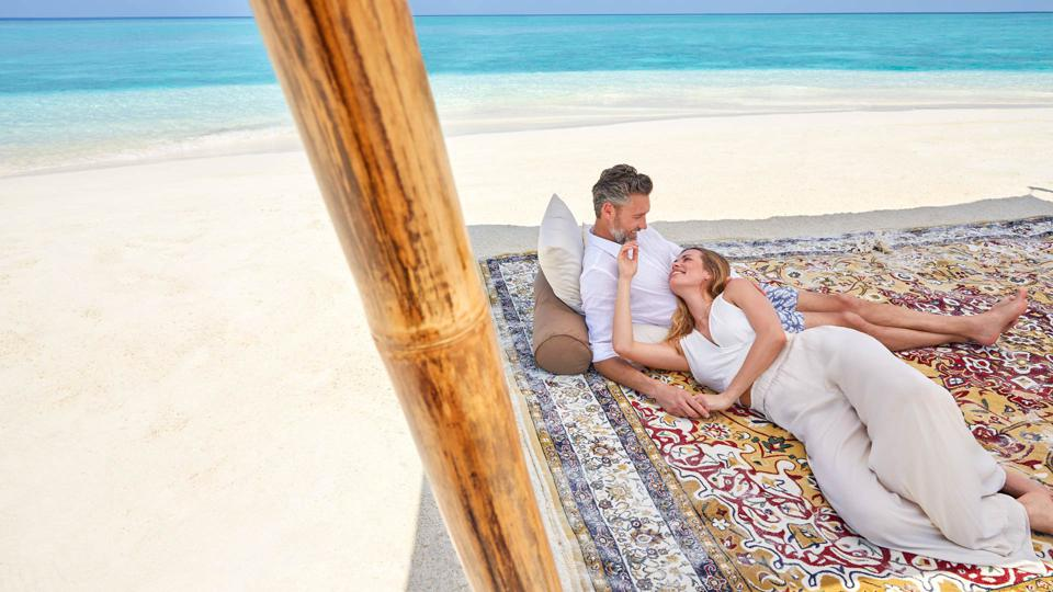 A couple on a blanket on a private island.