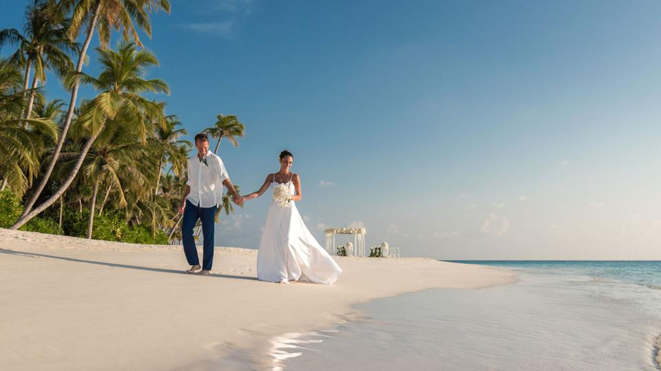 A newly married couple holding hands on Velaa Private Island.