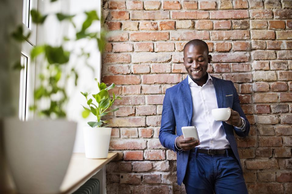 Smiling businessman using cell phone at brick wall by the window