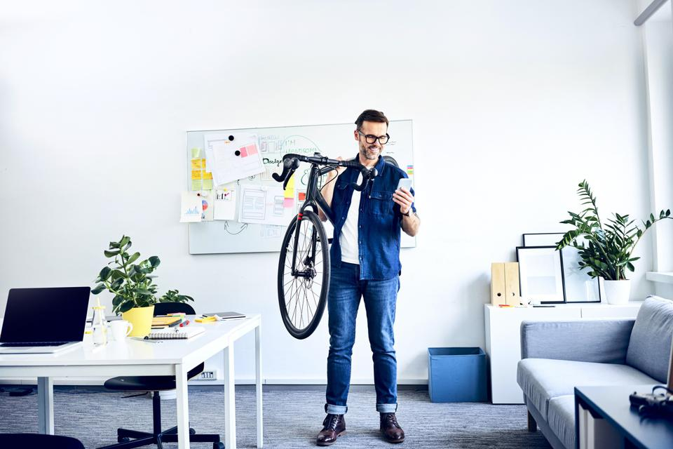 Smiling businessman carrying bicycle in office looking at smartphone