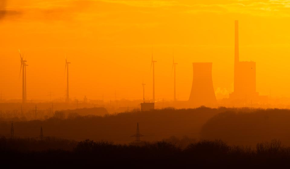 Dawn lights the Mehrum coal-fired power plant and adjacent wind turbines in Germany.
