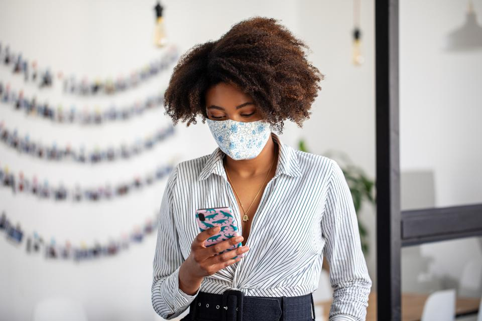 Businesswoman with face mask using mobile phone in office
