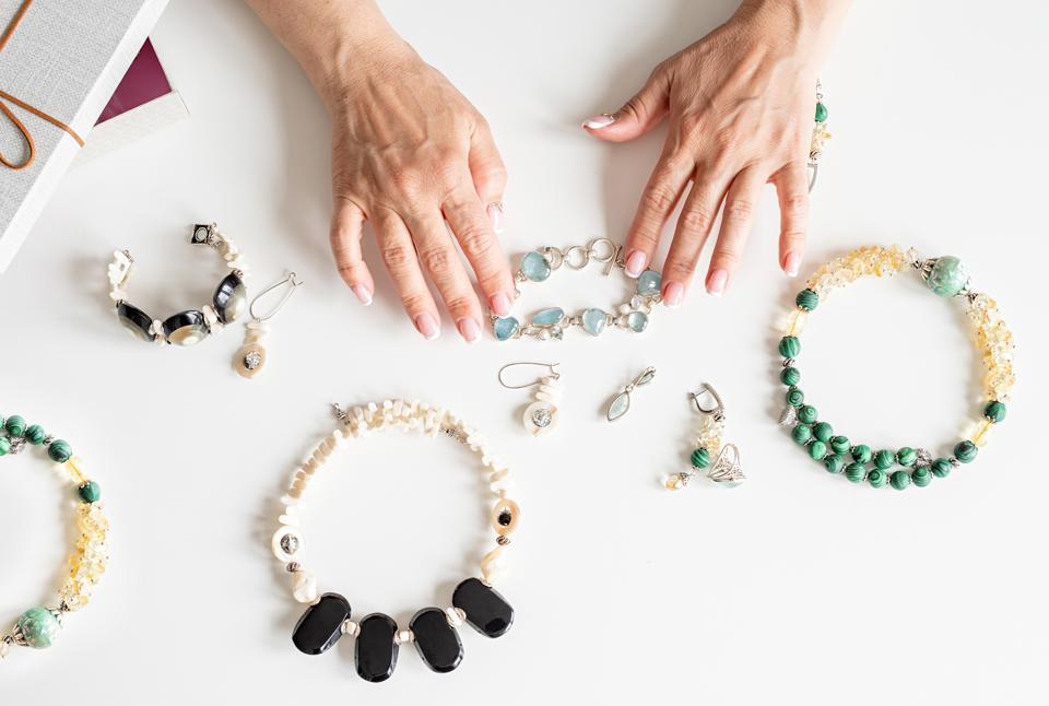 Hands of middle-aged woman touching various jewels top view