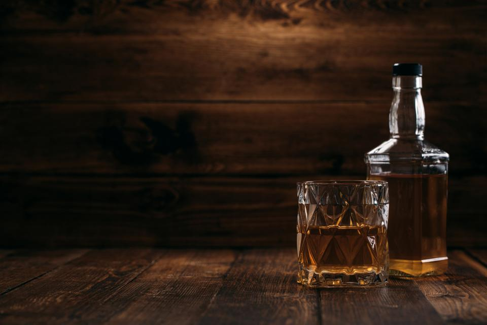 Elegant whiskey bottle with a full glass on a wooden background in retro style